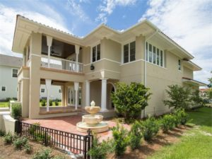 Large 2 story home with front terrace and fountain.