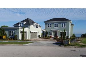 View of front of two story house with 3 car garage and ocean in background.